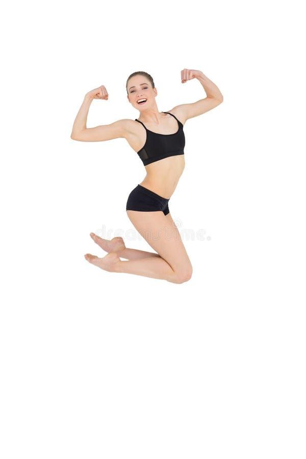 Forte modello esile che salta nell'aria che flette i suoi muscoli immagine stock libera da diritti