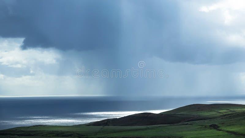 Forte pluie au-dessus d'océan calme à l'arrière-plan photographie stock libre de droits