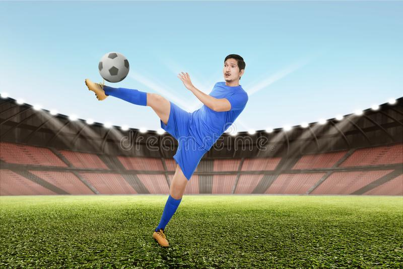 Forte scossa asiatica del calciatore la palla immagine stock