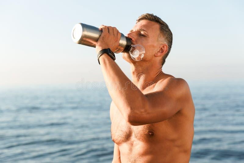 Forte sportivo maturo bello che beve sulla spiaggia fotografia stock libera da diritti