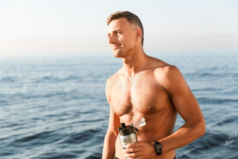 Forte sportivo maturo bello che beve sulla spiaggia fotografia stock