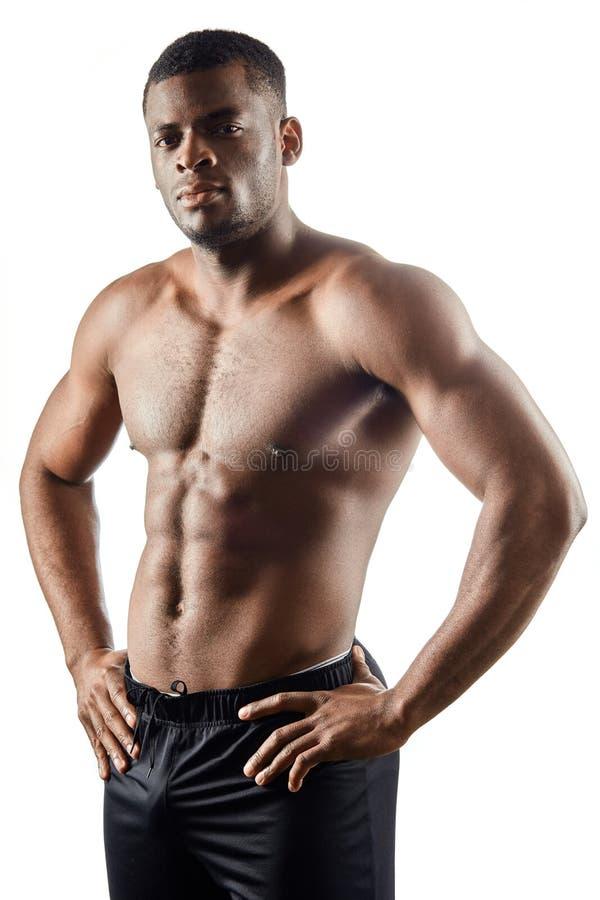 Forte tipo bello afroamericano con le mani sulle anche che loking alla macchina fotografica fotografia stock libera da diritti
