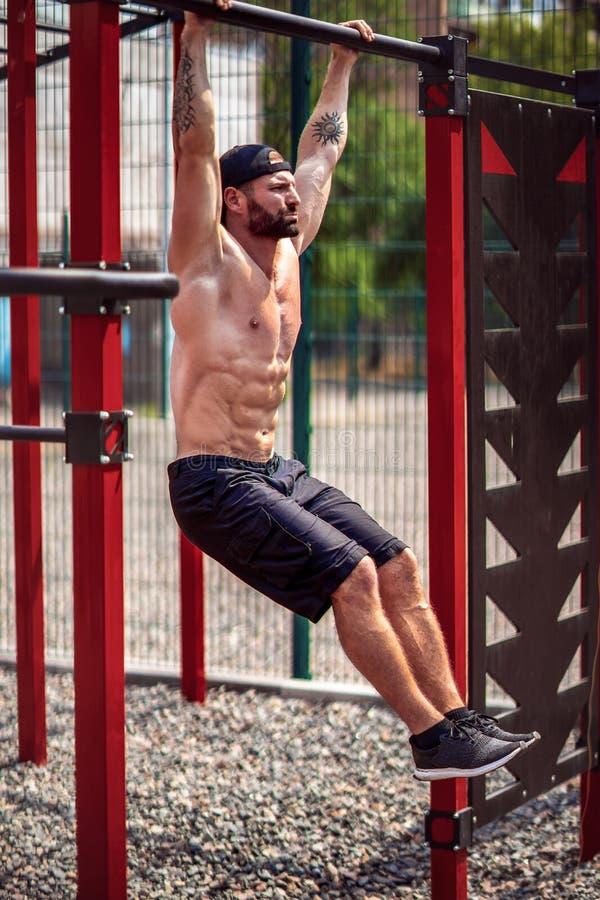 Forte uomo barbuto muscolare che fa esercizio addominale sulla barra orizzontale nel parco di estate forma fisica, sport, esercit fotografie stock