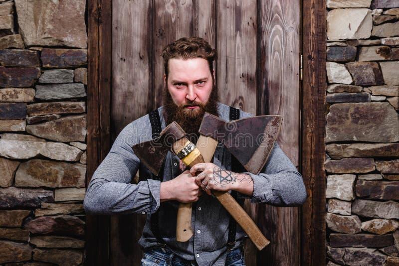 Forte uomo brutale con una barba e tatuaggi sulle sue mani vestite nei supporti alla moda dell'abbigliamento casual con due asce  fotografie stock