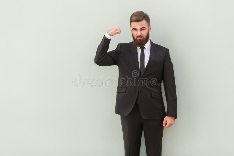 Forte, uomo d'affari seriamente barbuto che mostra muscolo e sguardo fotografia stock