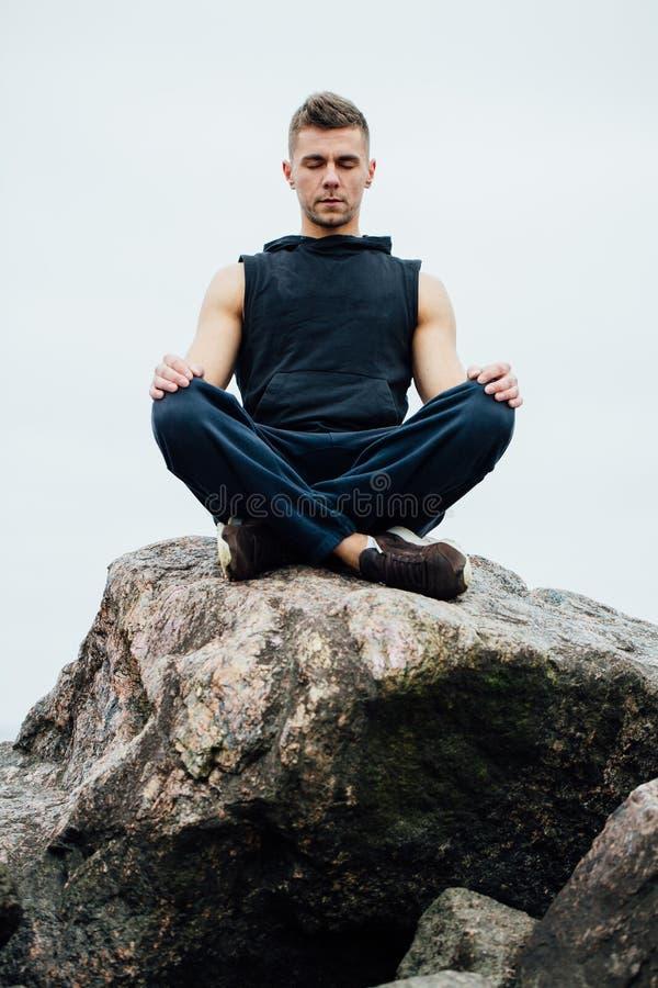 Forte uomo di yoga di forma fisica nella posa del loto sulla spiaggia della roccia vicino all'oceano Concetto armonico fotografia stock