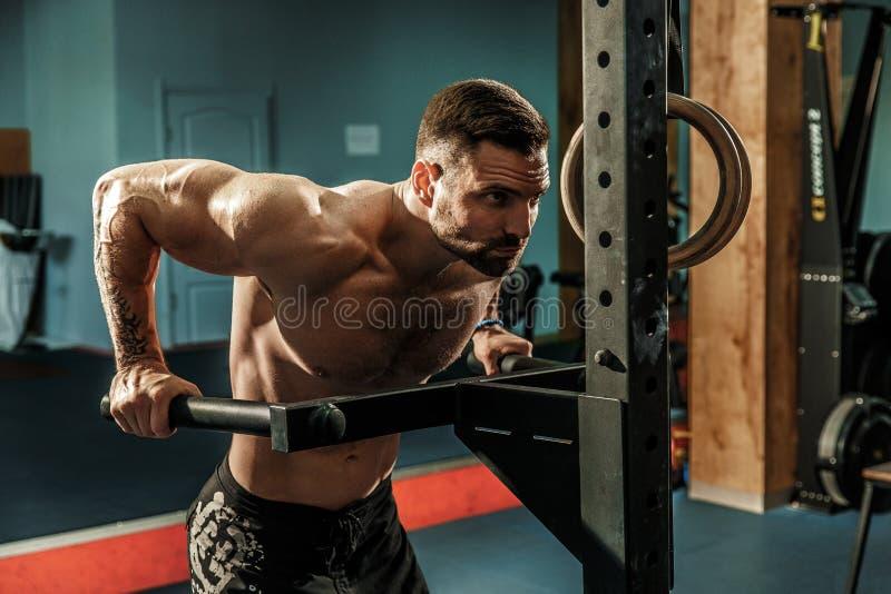 Forte uomo muscolare che fa spinta-UPS sulle barre irregolari nella palestra del crossfit fotografia stock libera da diritti