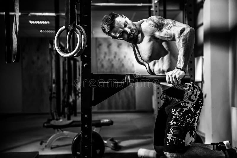 Forte uomo muscolare che fa spinta-UPS sulle barre irregolari nella palestra del crossfit fotografie stock libere da diritti