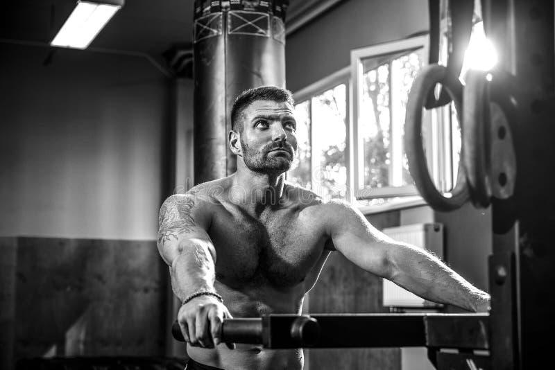 Forte uomo muscolare che fa spinta-UPS sulle barre irregolari nella palestra del crossfit fotografie stock