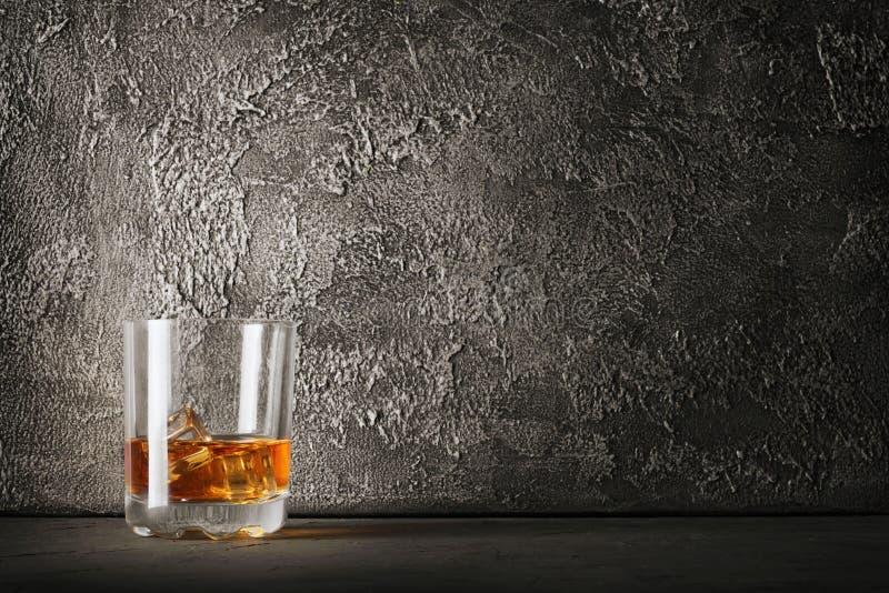 Forte whiskey scozzese della bevanda alcolica con il cubetto di ghiaccio in vecchio vetro di modo fotografie stock libere da diritti