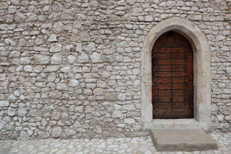Forteca, kasztel ściana robić brogujący kamieni bloki lub drewniany drzwi z gothic styl wskazującym łukiem zdjęcia stock