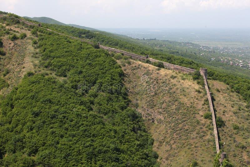 Forteca na rockowego mountainLong średniowiecznej kamiennej ścianie na wzgórzu ochraniać wioskę obrazy stock