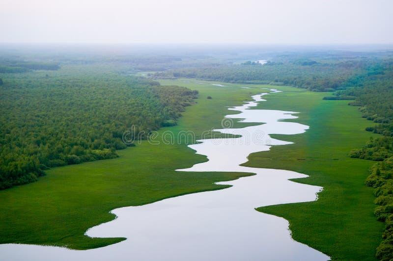 Fortemente meandrando o rio em um vale verde imagem de stock