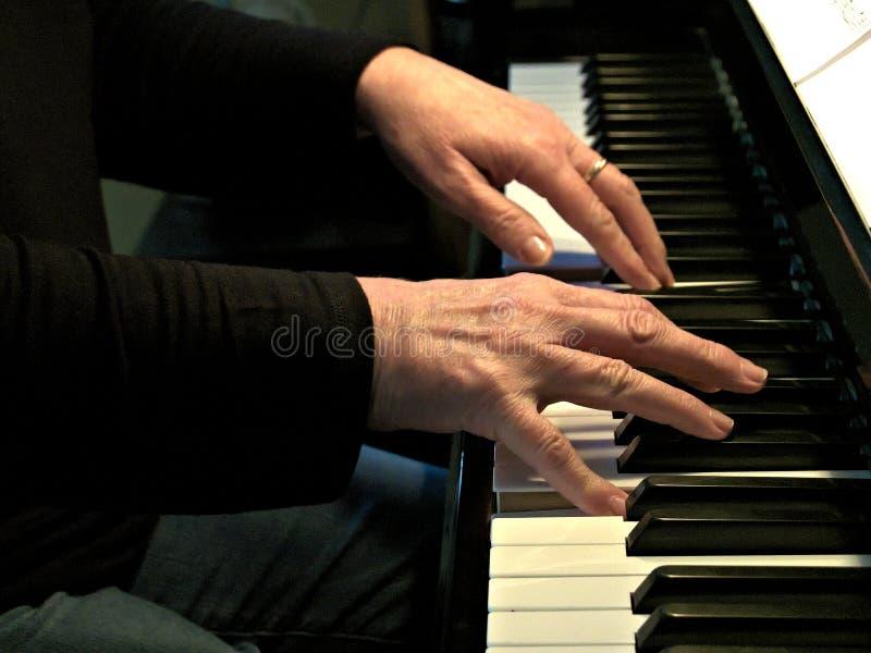fortepianowa bawić się starsza kobieta Zamyka w górę bocznego widoku starsze ręki i palce bawić się piosenkę obrazy stock