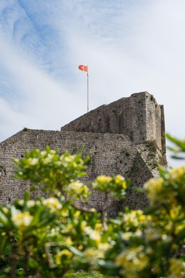 Fortezza antica, con la bandiera del Montenegro nella stazione turistica di Budua sulla riva della baia di Cattaro citadel Castel fotografia stock