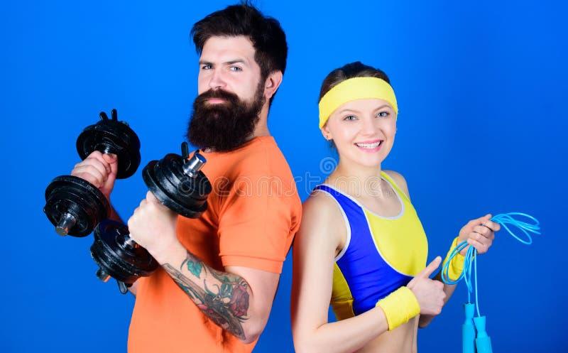 Forti muscoli ed ente Attrezzatura di sport Addestramento sportivo delle coppie con il bilanciere ed il salto della corda Forma f immagini stock
