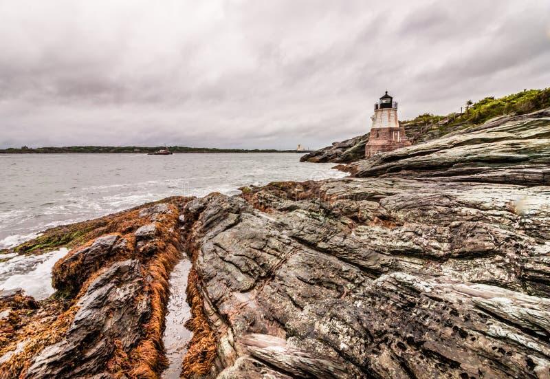 Fortifichi il faro della collina a Newport, Rhode Island, situato su una linea costiera rocciosa drammatica fotografia stock libera da diritti