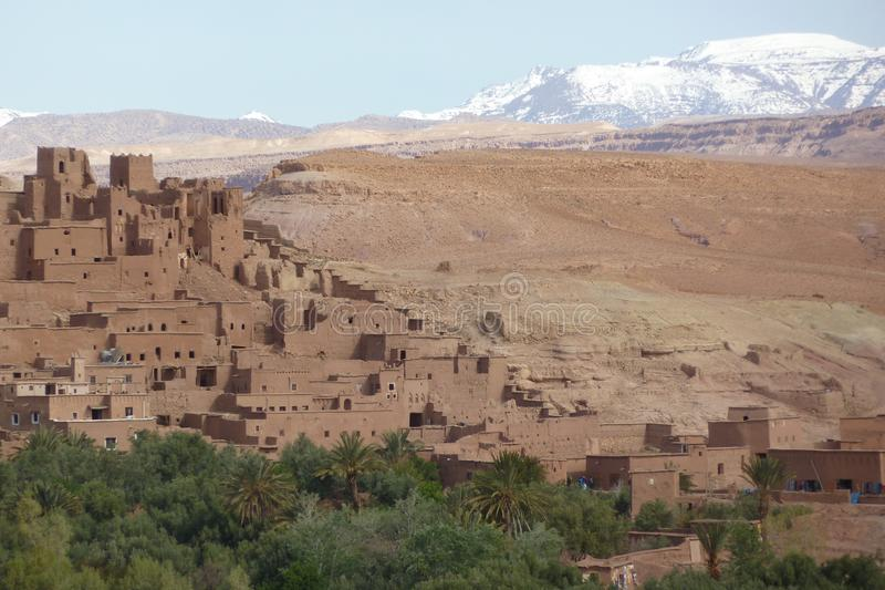 Fortified city of Ait Benhaddou along the former caravan route between the Sahara and Marrakech in Morocco with snow covered Atlas stock photos