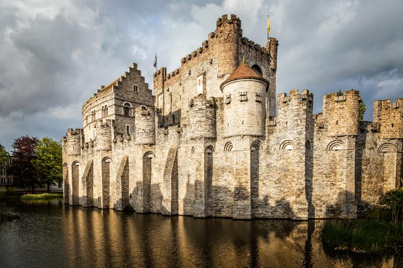 Fortified walls and towers of Gravensteen medieval castle with moat in the foreground, Ghent East Flanders, Belgium royalty free stock image
