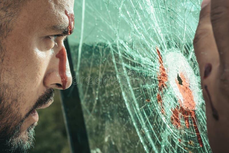 Fortleva en skada Latino man med sårskadan som ser till och med brutet exponeringsglas Latinamerikansk manblödning från huvudskad royaltyfri bild