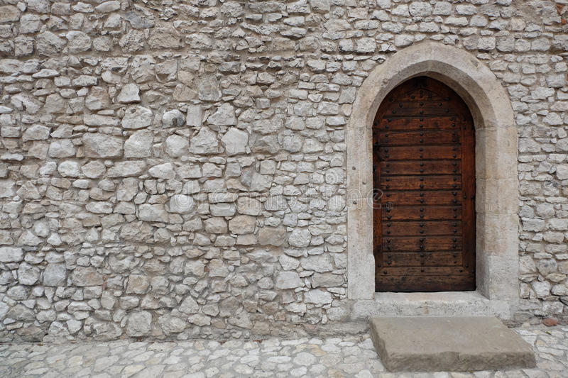 Fortress or castle wall made of stacked stone blocks and a wooden door with gothic style pointed arch stock photos