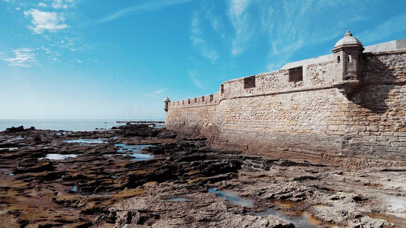 Fortress of San Sebastian, low tide and stones covered with alga stock photography