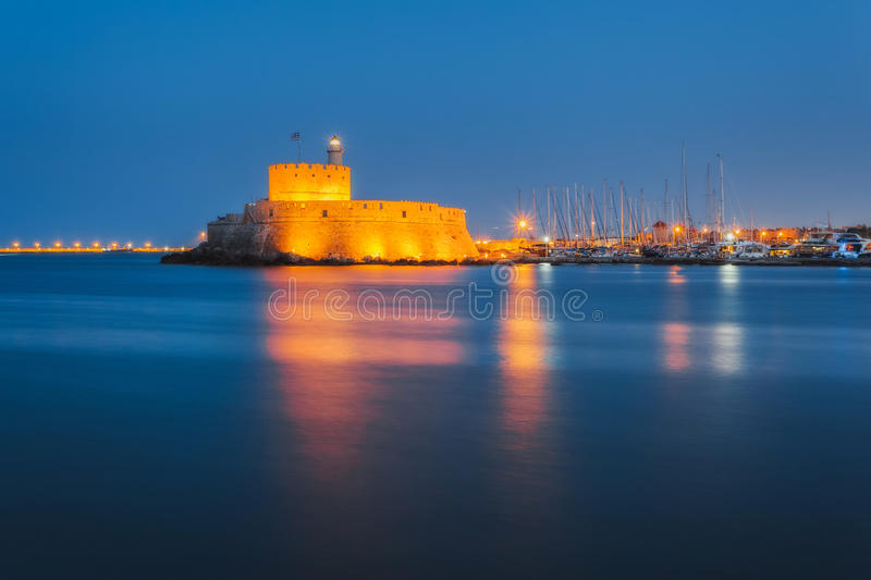 Fortress of St. Nicholas in the evening. Rhodes. Greece. Attraction of the island of Rhodes is the capital of the ancient port of Mandraki. Statue Colossus of stock image