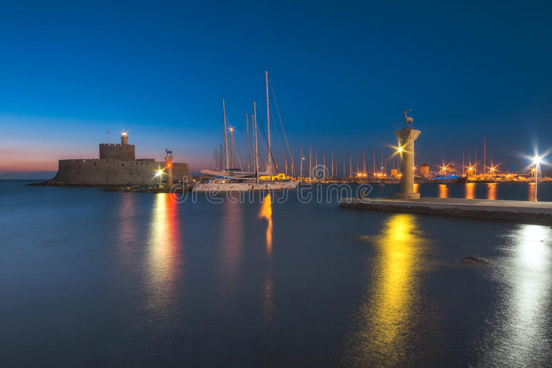 Fortress of St. Nicholas and sculpture Rhodes deer and deer at dawn. Rhodes Island. Greece. Attraction of the island of Rhodes is the capital of the ancient port stock images