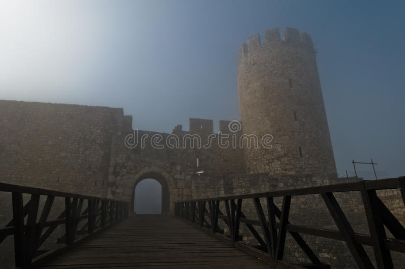 Fortress tower, gate and wooden bridge in fog at autumn sunny morning, Kalemegdan, Belgrade stock images