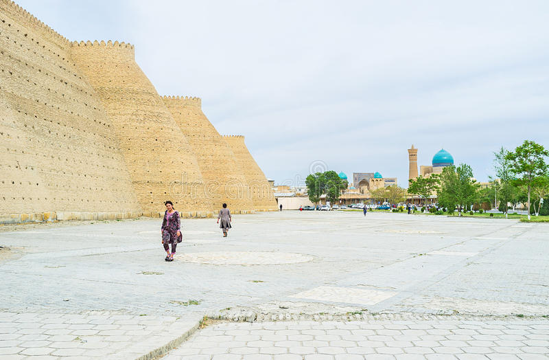 The fortress wall. BUKHARA, UZBEKISTAN - APRIL 28, 2015: The massive ramparts of the Ark fortress with the Po-i Kalyan complex on the background, on April 28 in royalty free stock photos