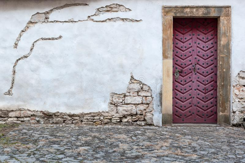 Fortress wall of a church Saint Wencesllas, Stara Boleslav, Czech Republic. Close-up look at the decorated color wooden door surrounded by white old wall stock photos