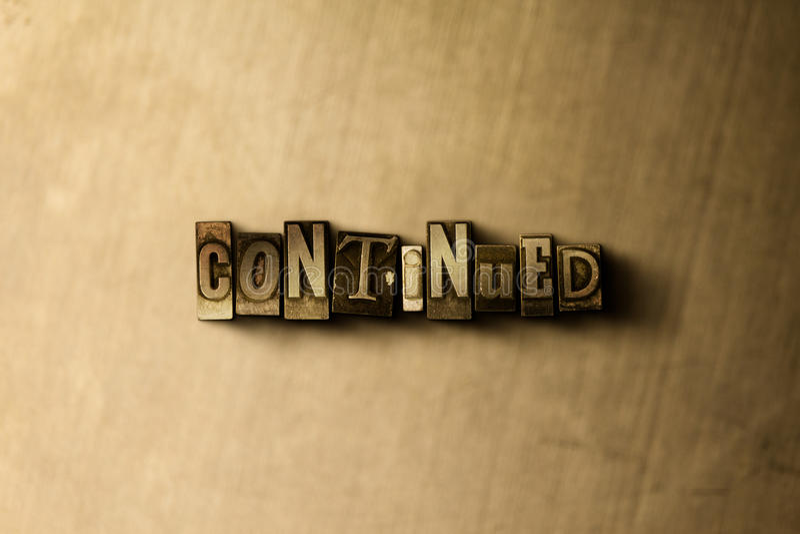 FORTSATT - närbild av det typsatta ordet för grungy tappning på metallbakgrunden royaltyfria foton