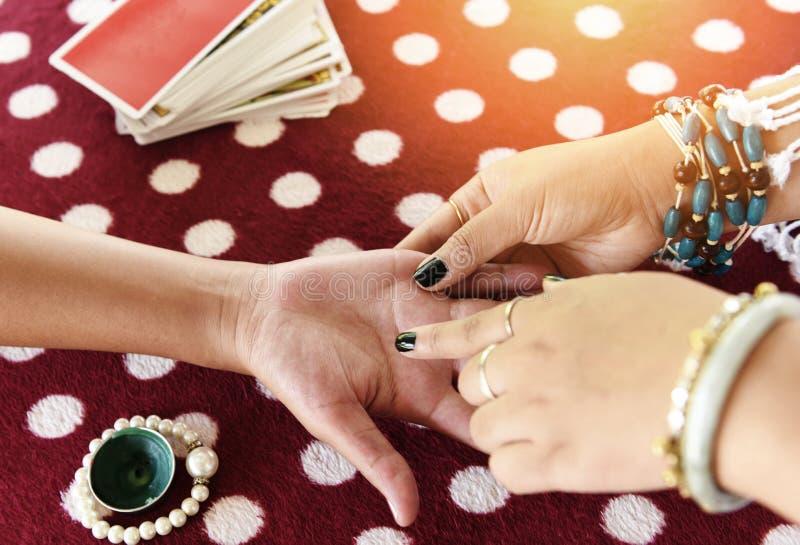 Fortuin-geldverteller leest fortuin-lijnen op hand Palmistry Psychische lezingen en clairvoyance handen met Tarot cards-verspreid stock fotografie