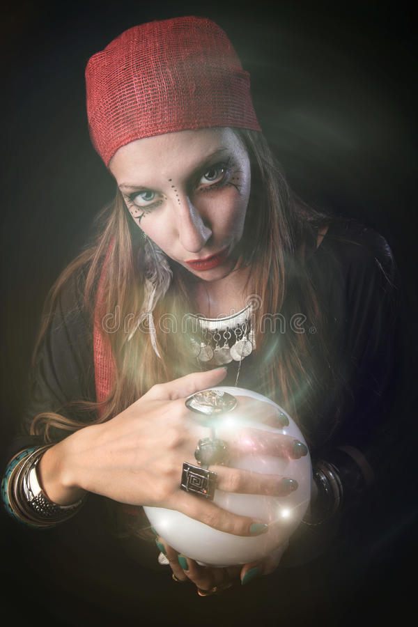 Fortuinteller die in een kristallen bol staren stock afbeeldingen