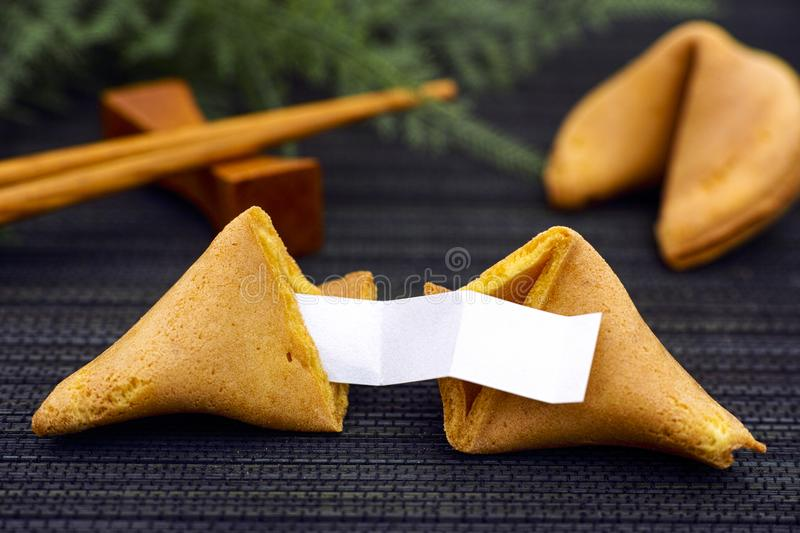 Fortune cookie with blank paper strip on black napkin background royalty free stock photography