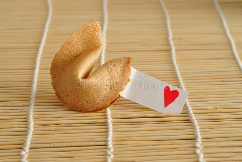 A fortune cookie with a piece of paper and a red heart royalty free stock photo