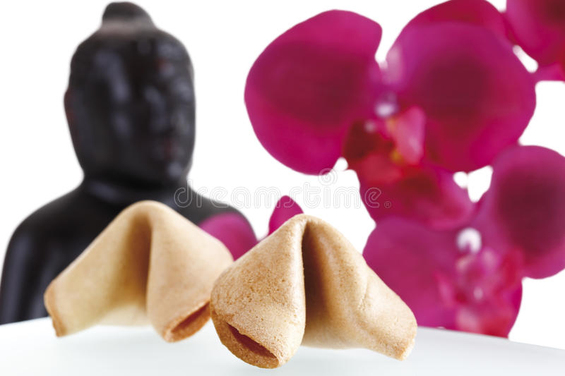Fortune cookies, buddha head and orchid leaves in background stock images