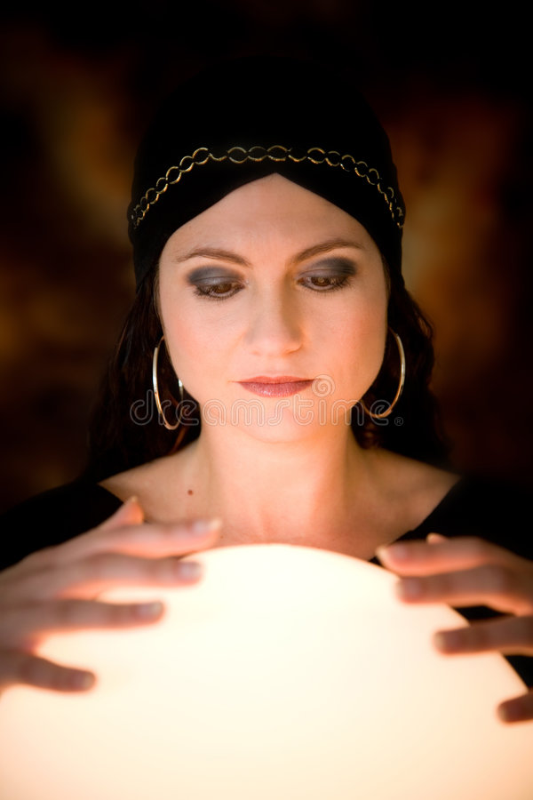 Fortune teller. Pretty gypsy woman with her hands on a crystal ball telling the future
