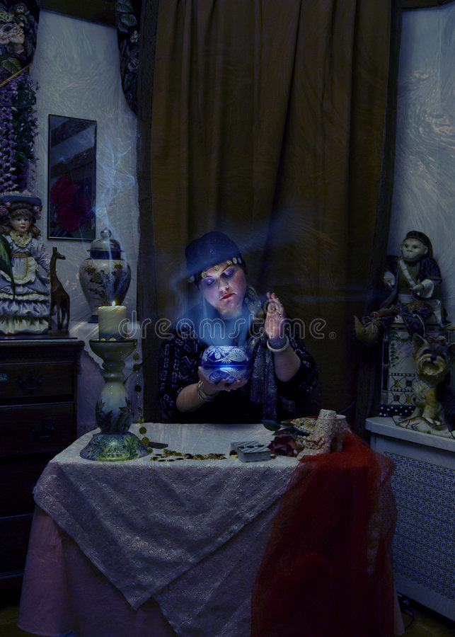 Fortune Teller. Mysterious fortune teller looking into crystal ball stock photo