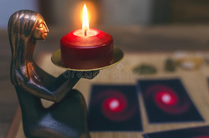 Fortune teller. Divination. Tarot cards. Blurred Tarot cards on the table with burning candle ahead. Future reading concept stock photo