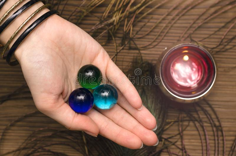 Future reading. Fortune teller concept. Fortune teller female hands with talisman gems on wooden table and candle. Divination concept stock photography