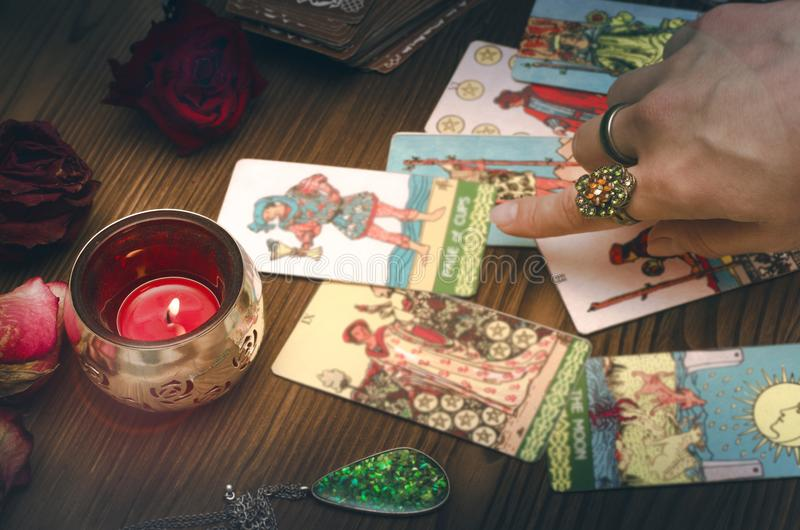 Tarot cards. Fortune teller female hands and tarot cards on wooden table. Fortune teller royalty free stock image