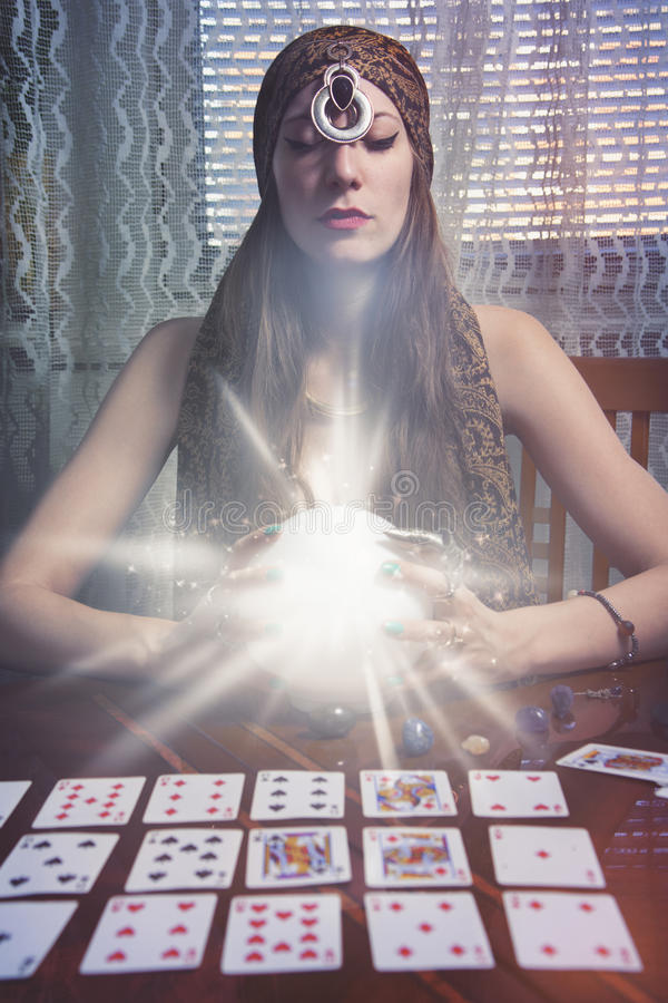 Fortune teller gazing in a crystal ball royalty free stock photography