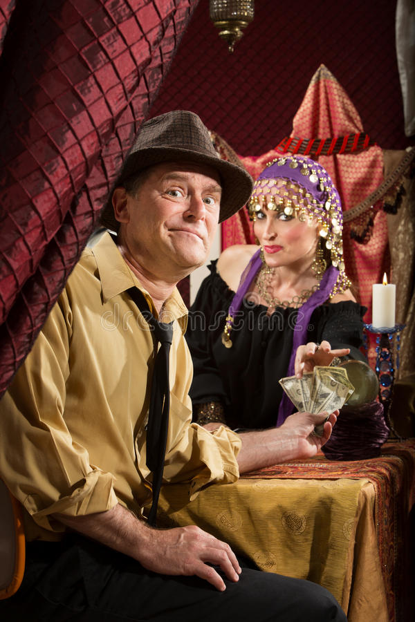Fortune Teller Getting Paid. Disappointed men paying fortune teller cash money royalty free stock image