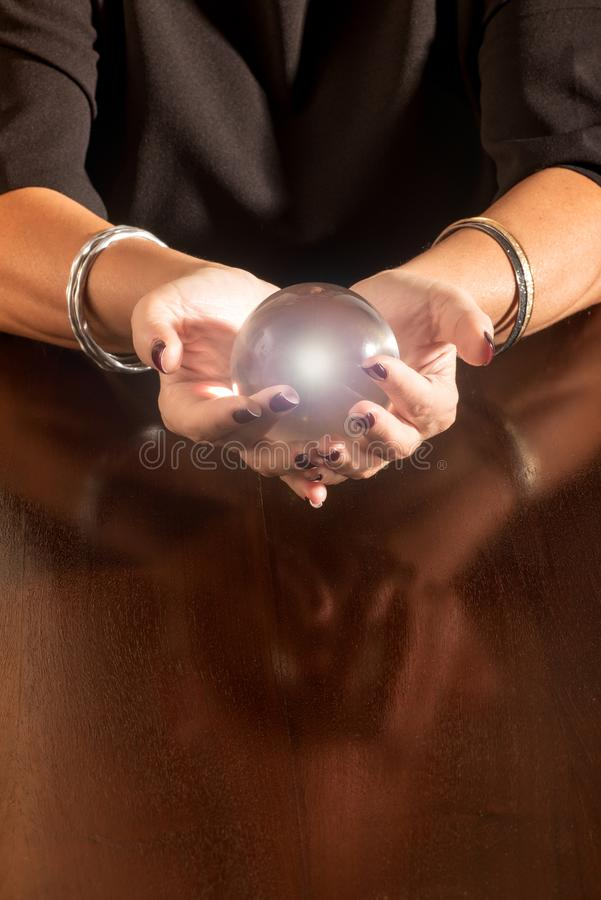 Fortune teller holding a glowing glass sphere stock photography