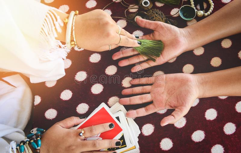 Fortune teller reading fortune lines on hand Palmistry Psychic readings and clairvoyance hands with Tarot cards divination. Fortune teller reading fortune lines stock image