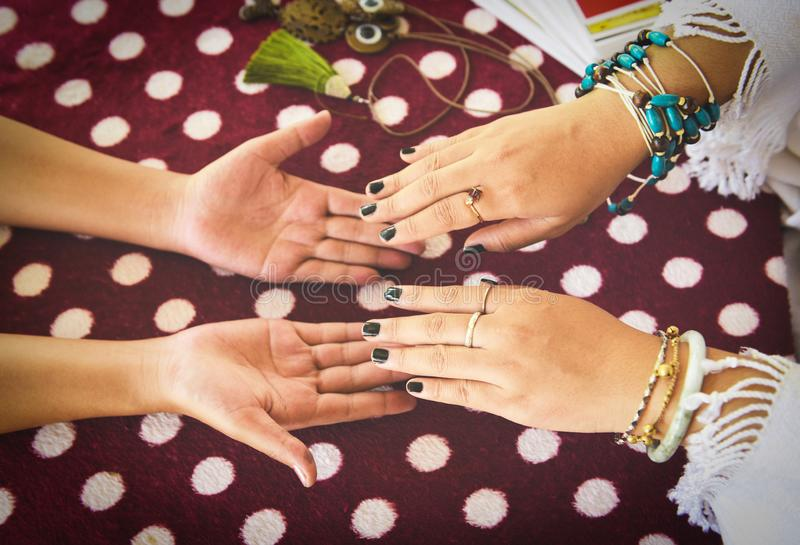 Fortune teller reading fortune lines on hand Palmistry Psychic readings clairvoyance hands concept with Tarot cards divination. Fortune teller reading fortune royalty free stock photo