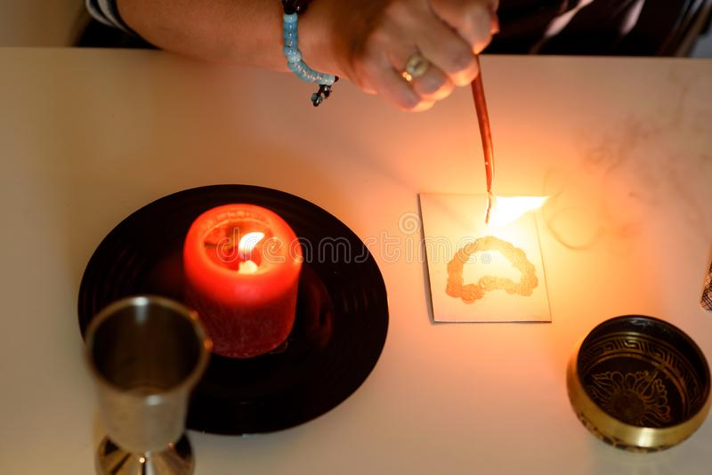 Portrait of beautiful middle age woman sits near a fortune teller desk with a tarot cards, black pendulum and candles. Fortune teller wonders on the candle stock photos
