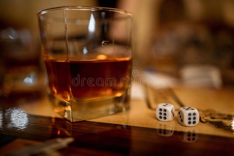 Fortune. Whisky glass and dice on table surface. Shallow depth of field royalty free stock photography