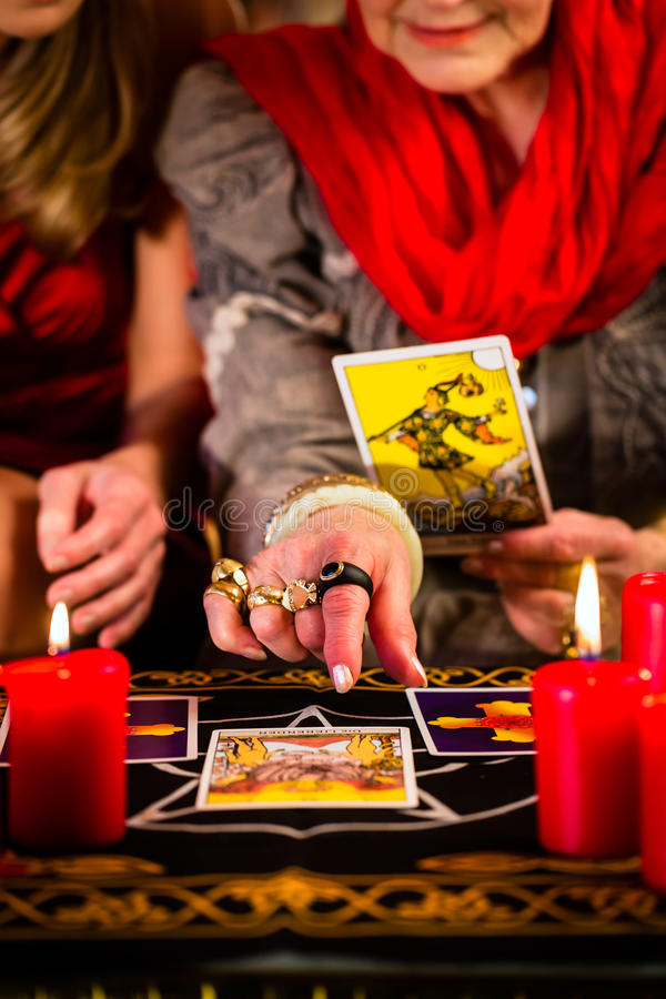 Fortuneteller που βάζει τις κάρτες Tarot με τον πελάτη στοκ εικόνα